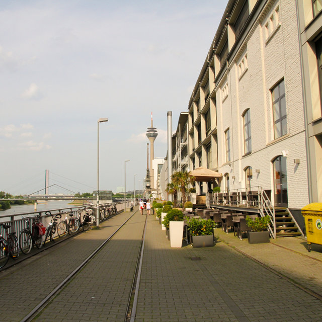 View along the Media Harbour quay. The Rheinturm telecommunications tower can be seen in the background.