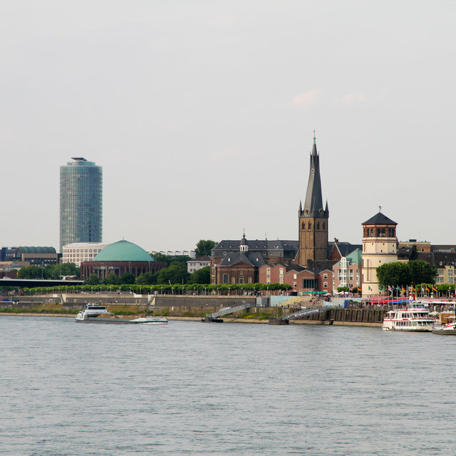View along the Rhine featuring the Schlossturm, the St. Lamberturs church, and the Tonhalle Düsseldorf.