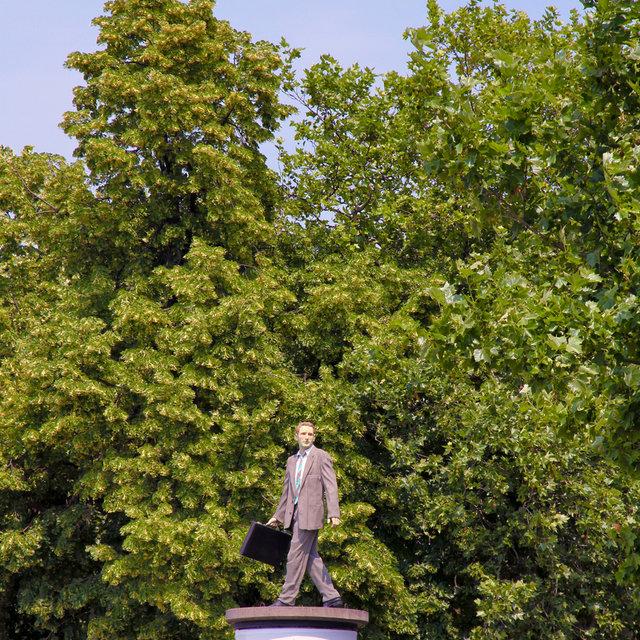 Businessman statue on top of an advertising pillar.