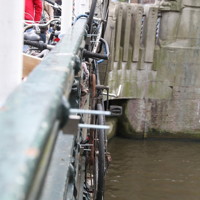 Bycicle hanging over the railing of a bridge in Amsterdam.