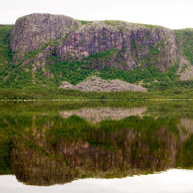 Mountain face mirroring in lake Saggat in Sweden.