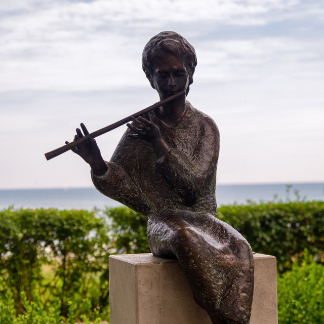 A statue of a boy playing the traverse flute at the beach in Binz.