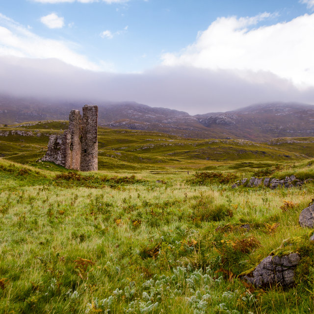 Ardvreck Castle in front of cloud covered hills.