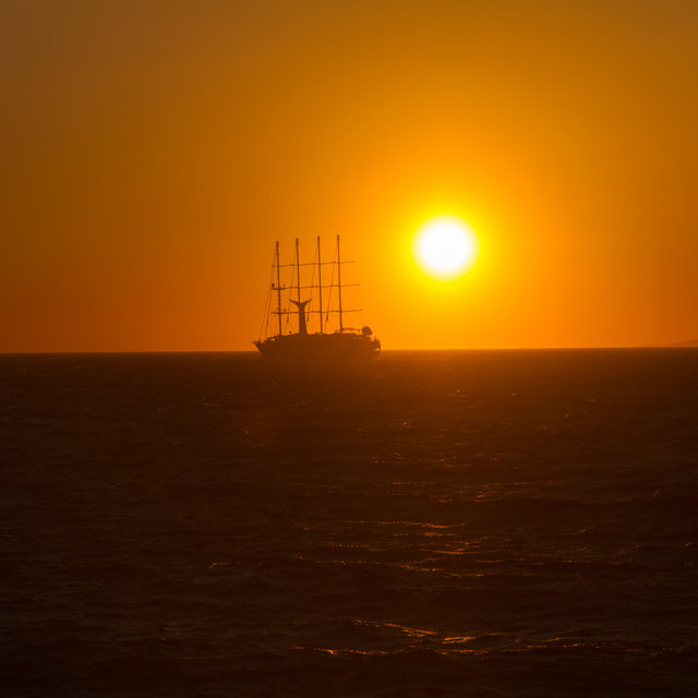 Sailing ship in front of the setting sun.