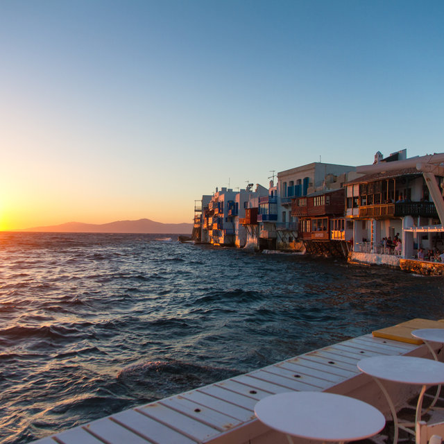 Setting sun and houses directly at the sea on Mykonos.