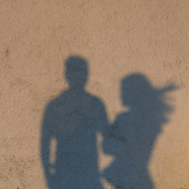 Shadow of a couple projected on a wall of a house by the setting sun on Santorini.