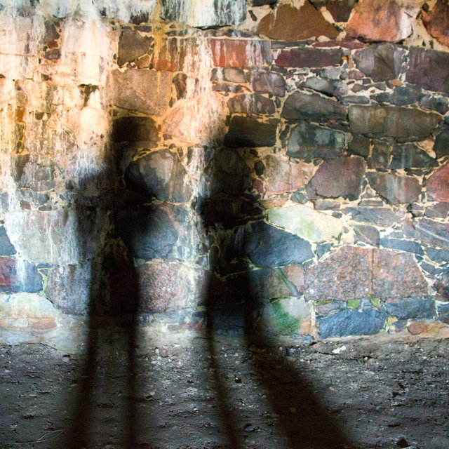 Shadows of two people on the walls of the catacombs on Suomenlinna.