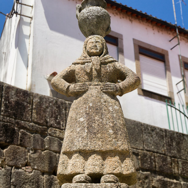 Stone statue of a women, balancing a jar on her head, in Ponte de Lima.