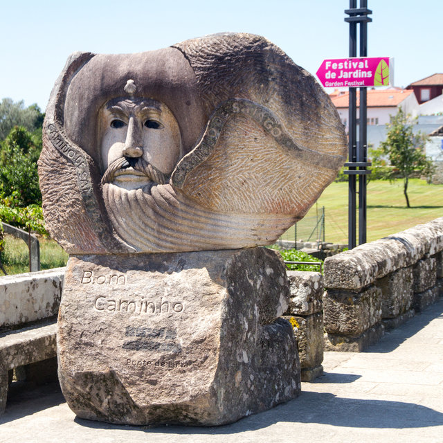 Stylized head monument on the west end of the Limia bridge.
