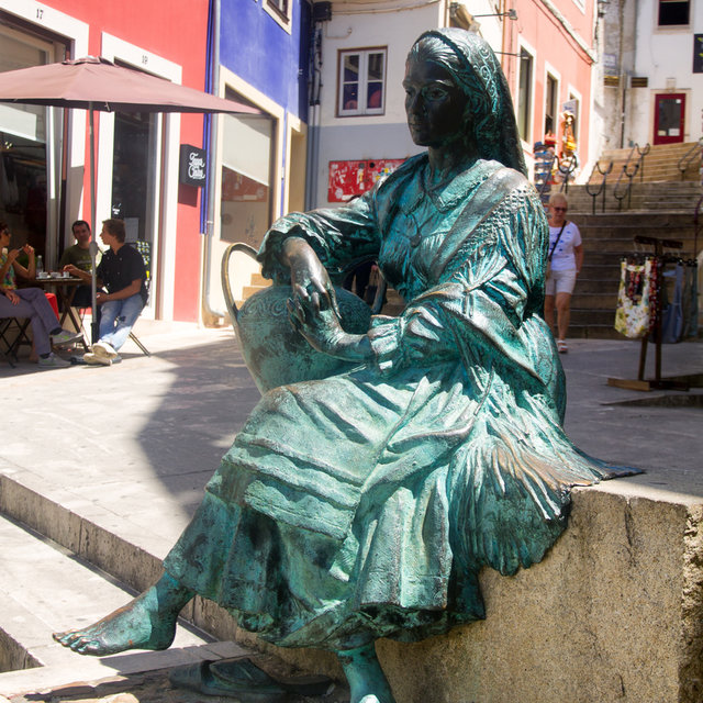A statue of a sitting woman in the streets of Coimbra.